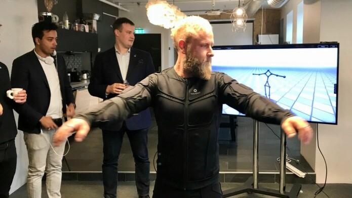 Leiar for Virtual Nordic Christian Instefjord prøver VR-dressen, medan Keith Mellingen (til venstre) og Dimitri Mikhalchuk ser på. (Foto: Lars Nyre)
