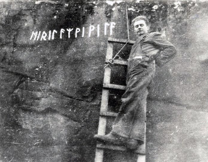 På denne innskriften står det «Jeg, erilen, Wiwila». Her ser du den kjente tindebestigeren Arne Randers Heen og innskriften på Veblungsnes i 1935 før den raste ut i fjorden. Runene var nok ikke malt hvite i virkeligheten, dette er sannsynligvis et tidlig eksempel på fotomanipulasjon. (Foto: Norsk Tindemuseum)