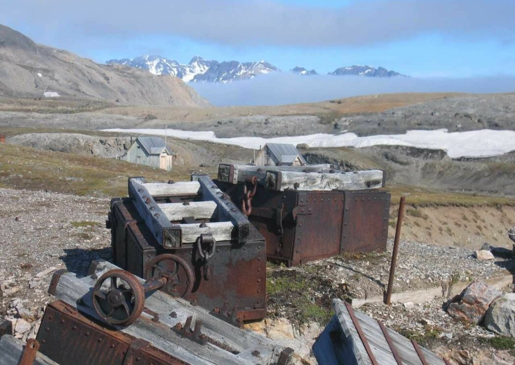 Fra anlegget ved marmorgruva «London» på Blomstrandøya som ligger i Kongsfjorden. Marmorbruddet ble anlagt i 1911. Det virket lovende, og en hel landsby ble bygget opp med flere boligbrakker til 70 arbeidere, smie, verksteder, en masse avansert utstyr og en liten jernbanelinje fra bruddet og ned til utskipningskaia som også hadde en lastekran. Dette bildet viser jernbanevogner som er veltet nede ved lastekaia, og i bakgrunnen, to av boligbrakkene som fortsatt står igjen i London. Dessverre viste det seg at marmoren ikke var så bra likevel, og bruddet ble lagt ned nesten før det var åpnet.