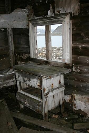 Dette bildet er fra fangsthytta i Svenskegattet. Den er bygget en gang mellom 1921 og 1924, og ble brukt av norske fangstfolk. Fangsthytta er fra den norske overvintringsfangsten. Denne hytta var hovedstasjon i dette området fra tidlig på 1920-tallet. Her står sengekøya fortsatt med rester av en madrass, kommoden står under vinduet, og kaffekannen ligger under boret. Riktignok er malingen skallet av og treverket nedbrutt, men man får likevel følelsen av at fangstmannen nettopp satte fra seg kaffekoppen og gikk ut for å se etter revefellene sine.