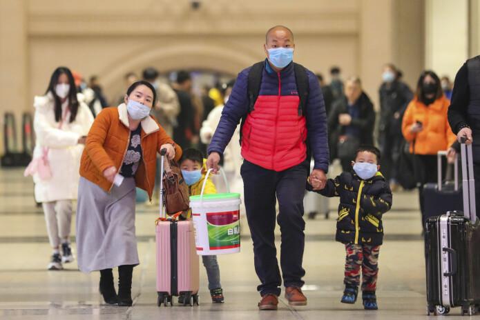 En kinesisk familie med munnbind på togstasjonen Hankou i Wuhan 21. januar i år.