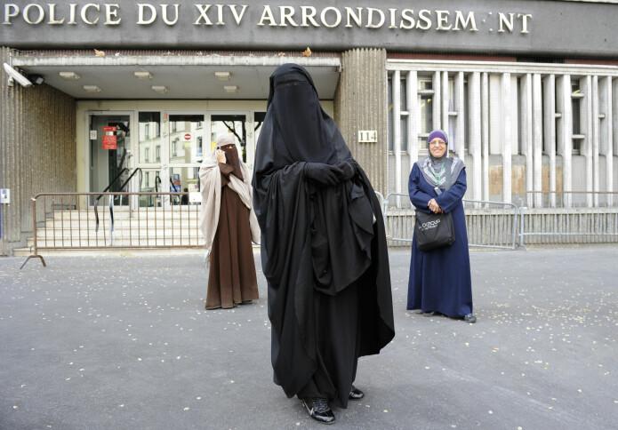 To kvinner med ansiktsdekkende plagg kommer ut av en politistasjon i Paris etter å ha blitt bøtelagt for klærne sine i april 2011.